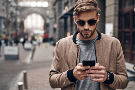 友達とおしゃべりしてる屋外に立っている間、彼のスマートフォンを使用してカジュアルな服を着てハンサムな若者 写真素材 - 91959924