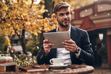 Young and successful. Good looking young man in smart casual wear using digital tablet and looking away with smile while sitting in restaurant outdoors Imagens