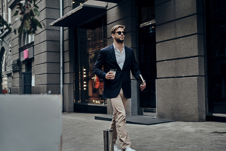 Handsome businessman. Handsome young man in smart casual wear carrying disposable cup while walking through the city street Imagens - 91959926