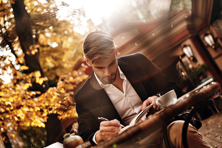 Everything must be planned. Good looking young man in smart casual wear writing something down in his personal organizer while sitting in restaurant outdoors Stock fotó