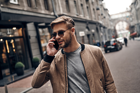 Nice talk with friend. Handsome young man in casual wear talking on his smart phone while standing outdoors