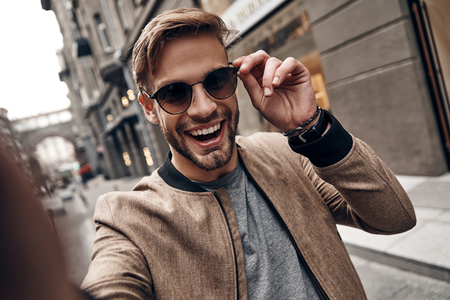Going crazy. Self portrait of handsome young man in casual wear smiling and adjusting his eyewear while standing outdoors Imagens - 91959928
