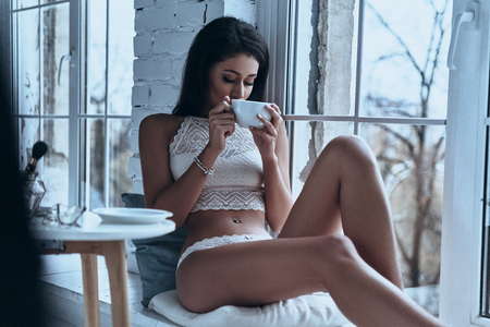 Just relaxing. Attractive young woman having morning coffee while sitting on the window sill at home