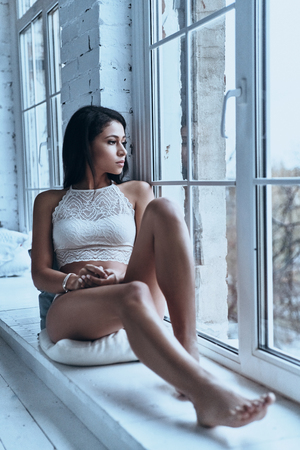 Quite contemplation. Attractive young woman looking away through the window while sitting on the window sill at home Imagens - 91959211