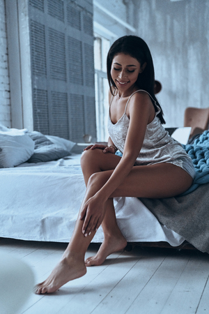 Her skin is so soft. Attractive young woman smiling and touching her leg while sitting on the bed at home Imagens