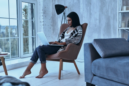 Blogging at home. Attractive young woman using her laptop while sitting in armchair at home Imagens