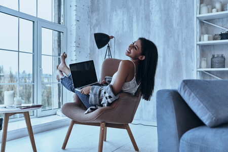 Enjoying every minute. Attractive young smiling woman looking away and using her laptop while sitting in armchair at home