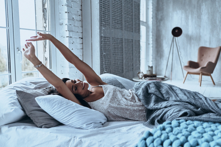 Nice morning. Attractive young woman smiling and stretching while lying on the bed at home