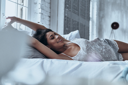 Time to wake up! Attractive young woman smiling and stretching while lying on the bed at home