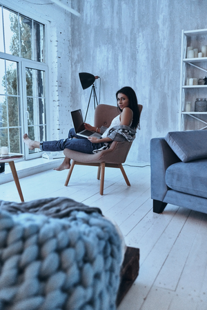 Carefree day at home. Attractive young woman looking at camera and using her laptop while sitting in armchair at home