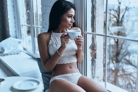 Enjoying nice day at home. Attractive young woman looking away through the window and having morning coffee while sitting on the window sill at home Imagens