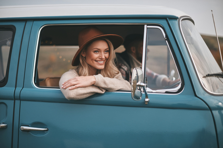 Doing what they love. Attractive young smiling woman looking out the vans window while enjoying the car travel with her boyfriend