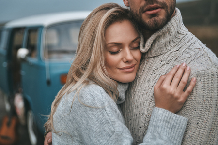 Feeling protected.  Beautiful young couple embracing and smiling while standing near the blue retro style mini van
