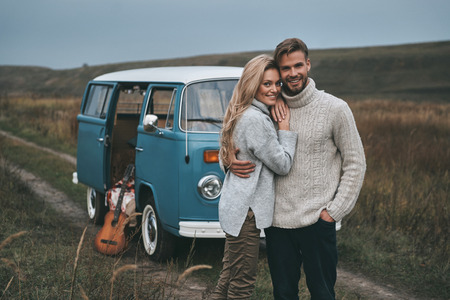 Happy to be together.  Beautiful young couple embracing and smiling while standing near the blue retro style mini van