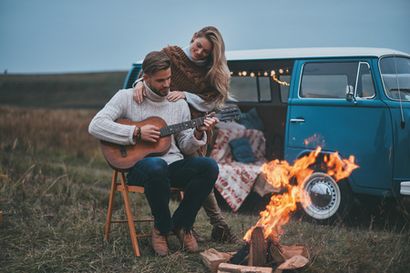 Love and trust.  Handsome young man playing guitar for his attractive girlfriend while sitting by the bonfire Imagens