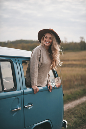 Life is awesome! Attractive young smiling woman leaning out the vans window while enjoying the car travel