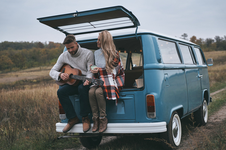 Romantic couple.  Handsome young man playing guitar for his beautiful girlfriend while sitting in the trunk of blue retro style mini van Imagens - 93567147