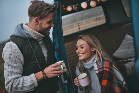 Making each other happy.  Handsome young man having hot drinks with his girlfriend while enjoying their road travel Imagens - 93567177