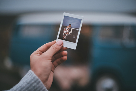 Perfect way to remember best moments.  Close up of young woman holding a photo of young couple while standing outdoors near the blue retro style mini van