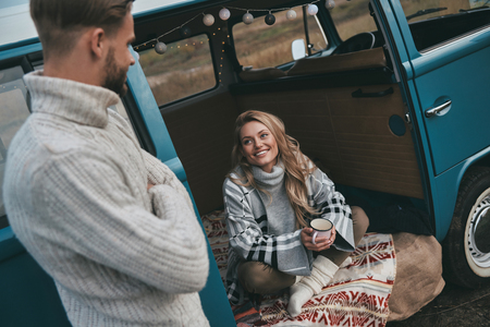 Leave all your worries behind!  Beautiful young woman looking at her boyfriend and smiling while sitting in blue retro style mini van