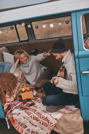 Admired by him.  Top view of handsome young man playing guitar for his beautiful girlfriend while sitting in blue retro style mini van