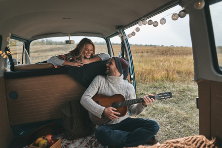 Do you like my new song?  Handsome young man playing guitar for his beautiful girlfriend while sitting in retro style mini van Reklamní fotografie