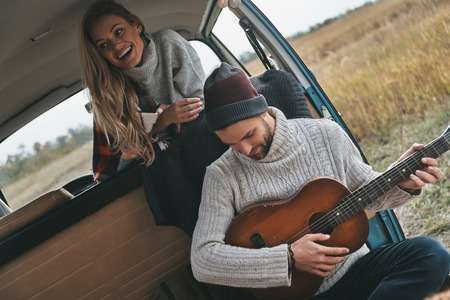 Enjoying happy moments. Handsome young man playing guitar for his beautiful girlfriend while sitting in retro style mini van