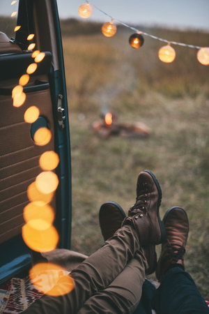 All they need is each other.  Close up of young couple resting inside of the retro style minivan while enjoying their road travel