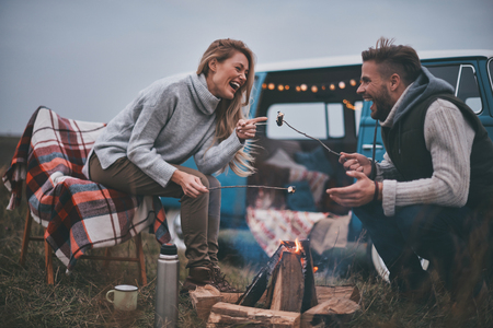 Resting after a long road.  Beautiful young couple roasting marshmallows over a campfire while enjoying their road travel