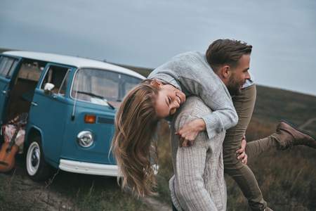 Crazy in love.  Handsome young man carrying his attractive girlfriend on shoulders and smiling while standing near the blue retro style mini van