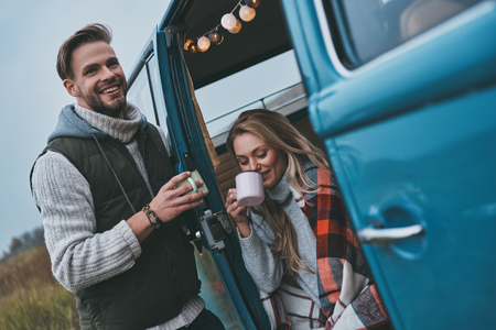 No cares and no rush.  Beautiful young couple having hot drinks and smiling while enjoying their road travel Imagens - 93628140
