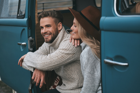 Enjoying every minute together.  Beautiful young woman looking at her boyfriend and smiling while sitting in blue retro style mini van