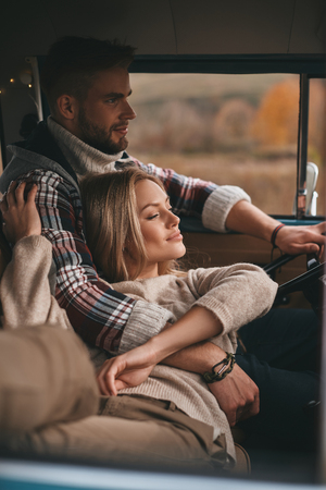 Nothing else but love. Attractive young woman resting and smiling while her boyfriend driving retro style mini van Stok Fotoğraf