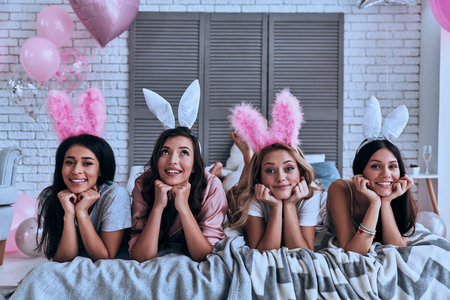 Pure beauties. Four attractive young women in bunny ears smiling while lying on the bed Stock Photo