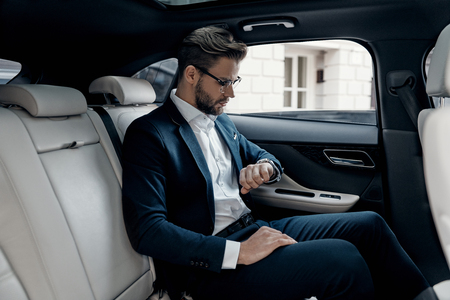 Keeping eye on time. Handsome young man in full suit looking at his watch while sitting in the car