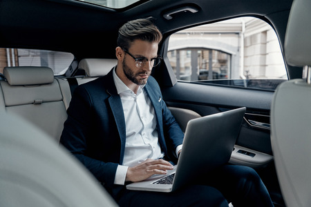 Full concentration at work. Confident young man in full suit working using laptop while sitting in the car Stok Fotoğraf - 93968310