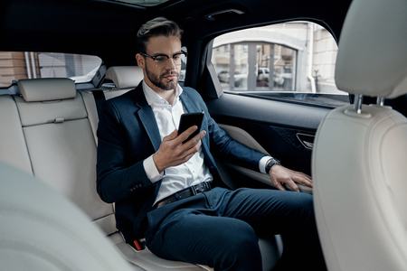 Young perfectionist. Handsome young man in full suit looking at his smart phone while sitting in the car