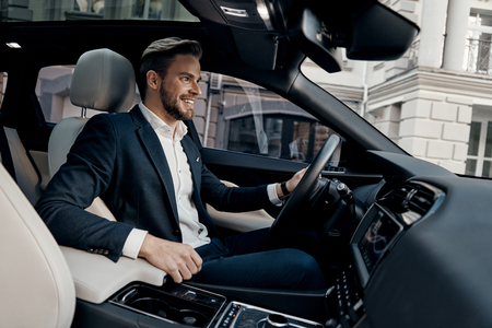 Always in a hurry. Handsome young man in full suit smiling while driving a car Фото со стока