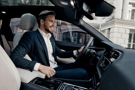 Zawsze w pośpiechu. Przystojny młody mężczyzna w pełnym garniturze uśmiecha się podczas prowadzenia samochodu