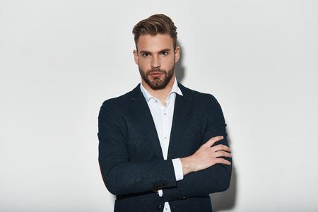 彼の完璧なスタイルに自信を持って。腕を組んで、灰色の背景に立っている間、カメラを見て、フルスーツのハンサムな若者