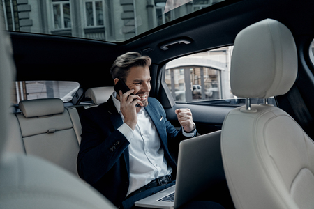 I can totally make it work! Handsome young man in full suit talking on smart phone and smiling while sitting in the car Stok Fotoğraf - 93968314