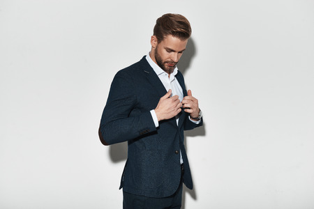 Perfect style. Handsome young man in full suit adjusting his jacket while standing against grey background Stock fotó