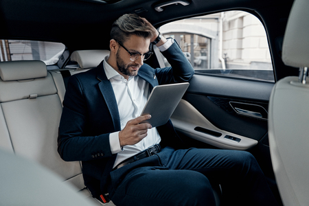 Considering the next step. Confident young man in full suit working using digital tablet while sitting in the car