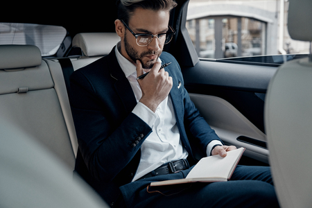 Thinking about business. Handsome young man in full suit writing something down in personal organizer while sitting inside of the car