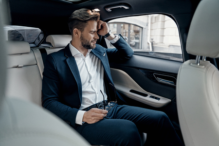 So tired. Frustrated young man in formalwear keeping eyes closed while sitting in the car