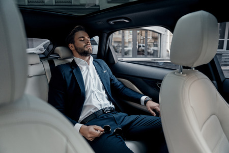 Feeling overworked. Tired young man in full suit keeping eyes closed while sitting in the car Banco de Imagens
