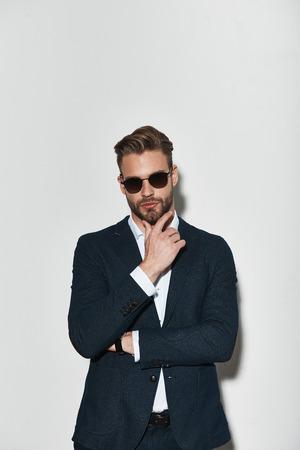 完璧に見えるように使用されます。灰色の背景に立ちながら顎に手を保つフルスーツのハンサムな若者 写真素材
