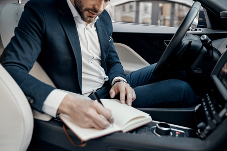 Business is his life. Close up of young man in full suit writing something down in personal organizer while sitting inside of the car