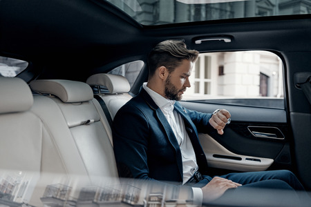 Just in time. Handsome young man in full suit looking at his watch while sitting in the car
