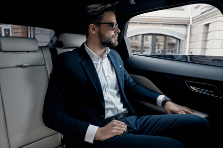 Busy day. Handsome young man in full suit looking through the window while sitting in the car Banco de Imagens - 100134640